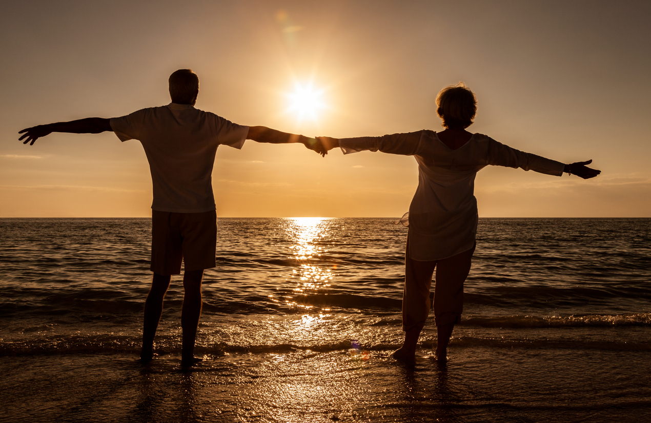 Senior man and woman couple holding hands arms wide at sunset or sunrise standing in the sea on a deserted tropical beach